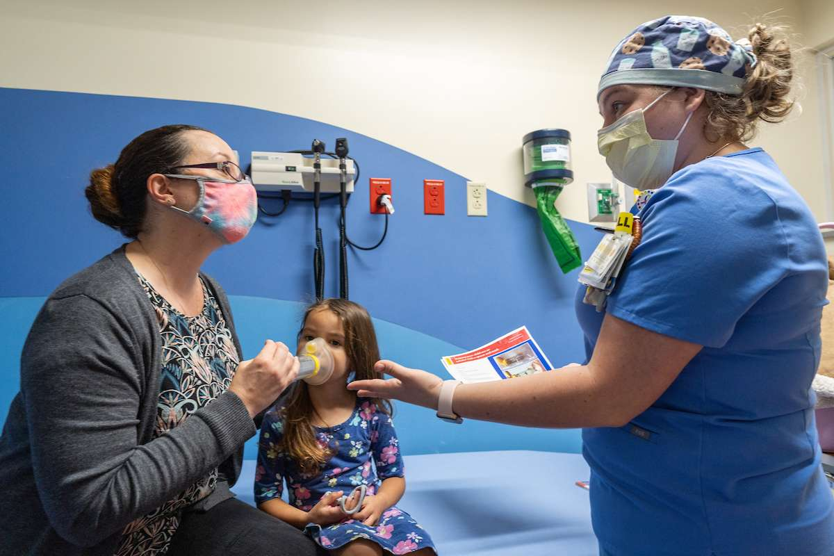 Jennifer Zimmerman, RN, explaining to a parent and her daughter how to use a bedside asthma action plan.